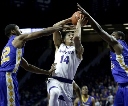 Kansas State's Justin Edwards (14) gets between Coppin State's Keith Shivers, left, and Blake Simpson to put up a shot during the first half, Wednesday, Dec. 9, 2015, in Manhattan, Kan.