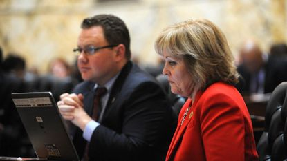 In the foreground, Republican House members Nic Kipke and Kathy Szeliga listen on April 13, 2015, to fellow delegates talk about the budget in the House chamber at the State House in Annapolis.