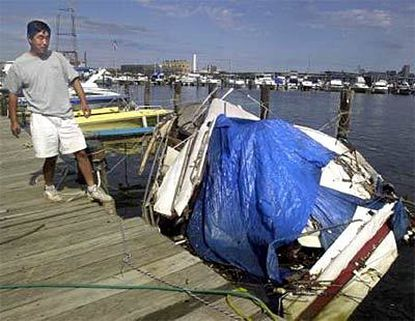 Charles Cao, owner of Middle Branch Marina, inspects a boat that was damaged during the storm. Although their businesses were affected, boatyard owners say they're grateful nobody was hurt.