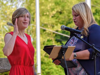Stacy Link, left, is sworn in as mayor of Sykesville by Carroll County Circuit Court Clerk Heather DeWees on Monday.