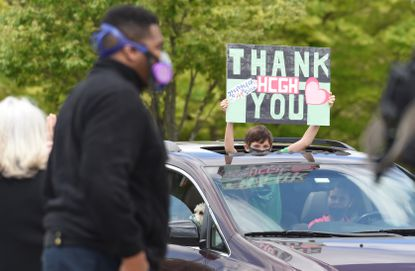 A boys holds a thank-you sign from the sunroof of a vehicle during a hospital appreciation caravan through Howard County General Hospital's campus on May 12.