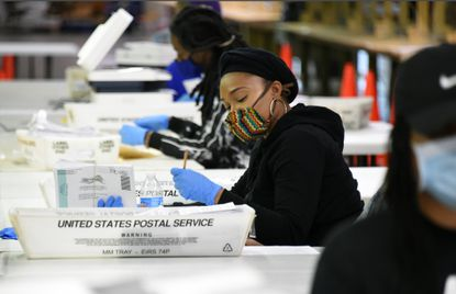 """Attorney General Brian Frosh says Maryland is part of a group of states suing the U.S. Postal Service to reverse """"unlawful"""" cost-cutting moves that Frosh said represent the """"most deceitful plan in American history to disrupt an American election."""" In this April 17, 2020, photo, a Baltimore City elections board staff member examines mail-in ballots at the board's West Baltimore warehouse."""