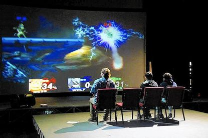 Players sit in front of video game at a Super Smash Bros. video game night in 2014.