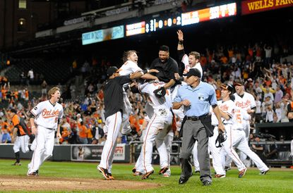 Orioles' Nolan Reimold (14) is mobbed by teammates after scoring the game-winning run in the ninth inning against the Boston Red Sox at Camden Yards on Sept. 28, 2011 in Baltimore. Baltimore won, 4-3.