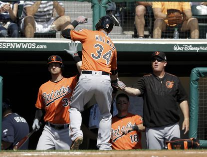 Orioles' Christian Walker (34) is greeted by coaches and players after hitting a home run in the third inning at a spring training baseball game against the Atlanta Braves, Tuesday, March 1, 2016, in Lake Buena Vista, Fla.
