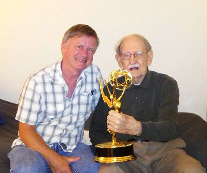 Catonsville native Dennis Towns poses with his father, Harold, 95, and the 2013 Emmy he won for Outstanding Sound Mixing for a Miniseries or Movie. The proud pair were photographed at the Brightview Assisted Living facility in Catonsville, where the elder Towns is a resident.