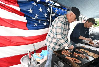 Dennis Cullison, left, and John Armacost with American Legion Post 200 cook breakfast sandwiches on grills during Hampstead Day and its return to the town's Main Street on Saturday, May 29, 2021.