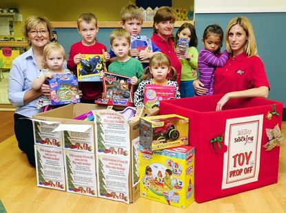 Adults and students from the Kiddie Academy in Forest Hill offer the boxes of toys collected for so far for the Empty Stocking Fund at the school Thursday morning. Donations of new unwrapped toys will continue to be collected at the school and at various other collection sites around the county through the upcoming holiday season.