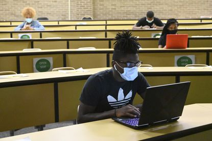 Jaheem Williams works on his laptop, with classmates spaced out behind him, during an oral communication class in a lecture hall in the Martin Luther King Jr. Communication Arts Center at Bowie State University on Wednesday, Sept. 9, 2020 in Bowie, Md. (Brian Krista/The Baltimore Sun via AP)