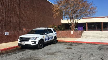 A police vehicle sits is parked near the main entrance to Joppatowne High School last month. The Harford County Sheriff's Office says four juveniles who are not students entered the school Tuesday morning and assaulted an 18-year-old student in the cafeteria.