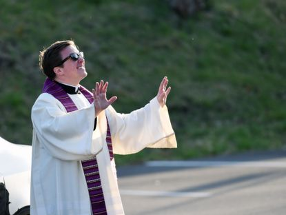 Fr. Tyler Kline participates in a drive thru confession outside Church of the Resurrection in Ellicott City during the season of Lent in the midst of the coronavirus pandemic.