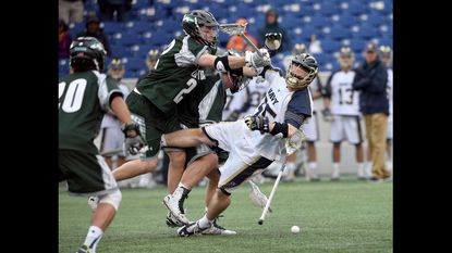 Loyola's Jack Carrigan sends Navy faceoff man Brady Dove to the turf, dislodging the ball in the first quarter. The Navy Midshipmen played the visiting Loyola Greyhounds in men's NCAA lacrosse on March 19, 2016at Navy-Marine Corps Memorial Stadium.