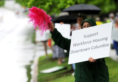 Leslie Glassberg, of Columbia, waves a pink pom-pom while joining a few dozen others in a May rally on Little Patuxent Parkway in Columbia for more affordable housing.