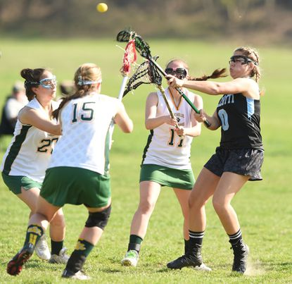 Pallotti's Jordan Shughrue, right, fires a shot on goal in the midst of a trio of Catholic defenders, from left, Julie Le, Rebecca Perry and Olivia Tuck during a girls lacrosse game at Herring Run Park on April 11. Shughrue leads the Panthers in scoring.