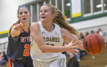 McDaniel's Liv Storer drives to the basket against Gettysburg's Ashley Gehrin in the first half of McDaniel's 66-57 loss Nov. 20, 2019, in Westminster.