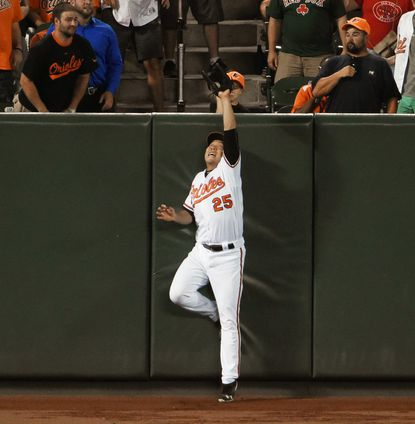 Baltimore, MD.--9/20/16-- Orioles' Hyun Soo Kim reaches over left-field fense to catch a long fly ball by Red Sox's Mookie Betts in the ninth inning.
