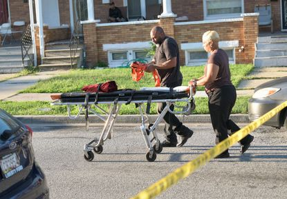 Technicians from the medical examiner's office arrive at the scene where one person was killed and three wounded at a home in the 1600 block of 29th St.