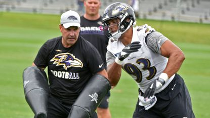 Defensive line coach Joe Cullen works with #93 DE Chris Wormley during Ravens training camp on Monday.