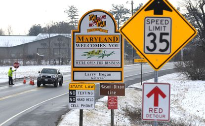 State Highway crews replace former Gov. Martin O'Malley's name on road signs with that of newly inaugurated Gov. Larry Hogan along York Road in Freeland.