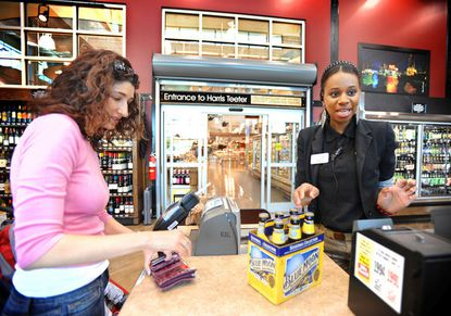 "Melinda Goodman, left, buys beer from Tonya Williams, wine consultant at The Cellars, a liquor store in McHenry Row. Then she goes to Harris Teeter through the entryway from the liquor store (background) to do some grocery shopping. Goodman thinks the opening that joins the stores is ""great, very convenient."""