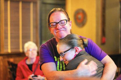 Shedding tears, Kirsten Coombs embraces her daughter, Lilly, after securing a seat on the board on Nov. 8.