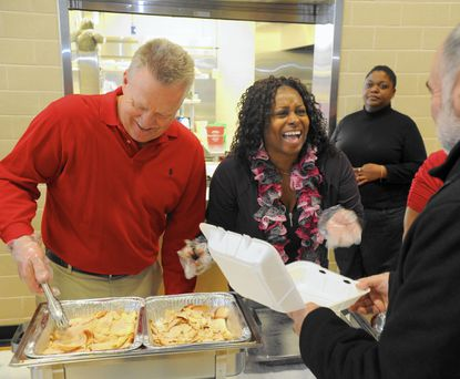 Volunteers Larry Kropff, left, and Dora Suber, right, share a laugh with another volunteer as they prepare meals during the Thursday's Thanksgiving dinner at St. Margaret Church in Bel Air.