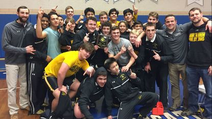The Mt. Hebron wrestling team and coaches pose with the 3A East regional championship plaque after defeating J.M. Bennett and Atholton at Stephen Decatur High School on Thursday, February 8, 2018 to win its first region title since 2002.