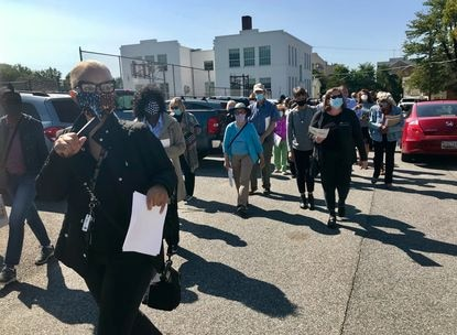 Nancy Goldring, president of the Northeast Towson Improvement Association, leads about two dozen attendees on a Sept. 22 tour of Historic East Towson. The tour was organized as part of an effort by residents of East Towson and the Harris Hills condominium complex to resist a proposed 57-unit affordable housing complex they say will exacerbate flooding issues, school overcrowding and traffic congestion on East Joppa Road.