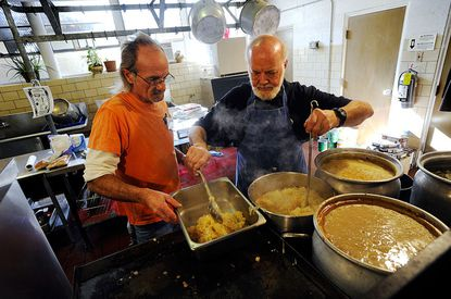 """Joe """"Rocky"""" Bowers, left, and Cal Bloom prepare food for The Shepherd's Staff Thanksgiving Day Community Dinner at St. John Catholic School in Westminster Thursday."""