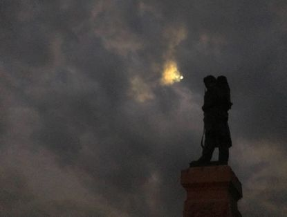 Before sunrise on the 157th anniversary of the famous battle, the moon appears through clouds over one of the monuments at Antietam.