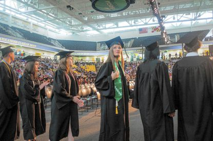 Grace Collins looks for her family in the audience as she prepares to walk the stage for Carver Center for the Arts and Technology's graduation at Towson University on May 27.