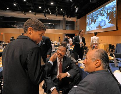"""Chase Allen, 11 talks to law firm head William """"Billy"""" Murphy, Jr. (foreground right) and Md. congressman Kweisi Mfume (D-7th), both who worked as paperboys for the Afro-American newspaper."""