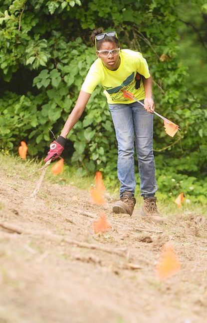 Chloe Outen, 19, of Laurel, marks the areas where other crew members will dig a rain garden at Oakland Mills Interfaith Center.