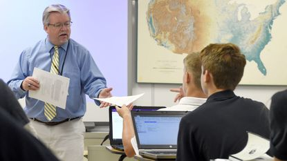 On Aug. 29, this school year's first day, Tom Durkin, John Carroll's new principal, hands out a syllabus in the English class he teaches. Durkin also recently handed out guidelines requiring he or the school's marketing director pre-approve all stories in the school newspaper.