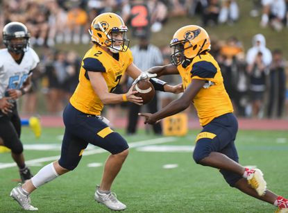 Catonsville's Jacob Diluca, shown handing off to Anthony Fliggins in a 2019 game, returns at quarterback for the Comets who open their season against Perry Hall.