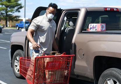 Josh Wallace wears a N95 mask as he loads groceries into his truck after shopping at Trader Joe's in Annapolis. Many in the Annapolis area are taking heed and wearing facial coverings and masks when out in public to help prevent the spread of COVID-19.
