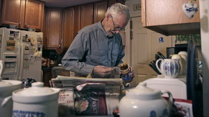 In this Nov. 22, 2019, photo, Charles Flagg, who is stricken with Alzheimer's disease, makes a peanut butter sandwich for lunch at his family home in Jamestown, R.I. He is participating in a study on the drug Aducanumab. New results were released on the experimental medicine whose maker claims it can slow the decline of Alzheimer's disease, the most common form of dementia.