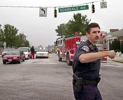 Police officer Bill Taylor (right) directs traffic at Harford and Echodale avenues, where signals were still out yesterday morning. A fire engine responds to a fender-bender at the intersection.