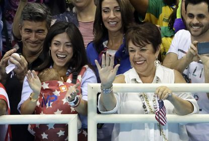 The family of Michael Phelps, mother Debbie, right, and his fiance Nicole Johnson holding their baby Boomer during the swimming competitions at the 2016 Summer Olympics.