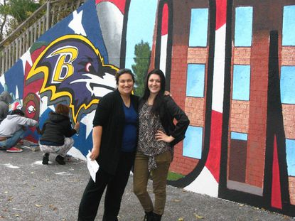 Owings Mills High School art teachers Mary Elizabeth Dickman, left, and Meghan Manniso have mentored students painting a mural on a retaining wall at at a Jiffy Lube in Owings Mills.