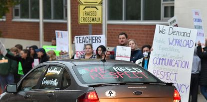 A vehicle participating in the Harford County Education Association car caravan showing support for teachers rolls by the Harford County Public Schools A.A. Roberty building on Hickory Avenue in Bel Air Monday evening as a group of folks with Reopen Harford County Schools and other reopen schools groups gather outside the building during the Board of Education meeting.