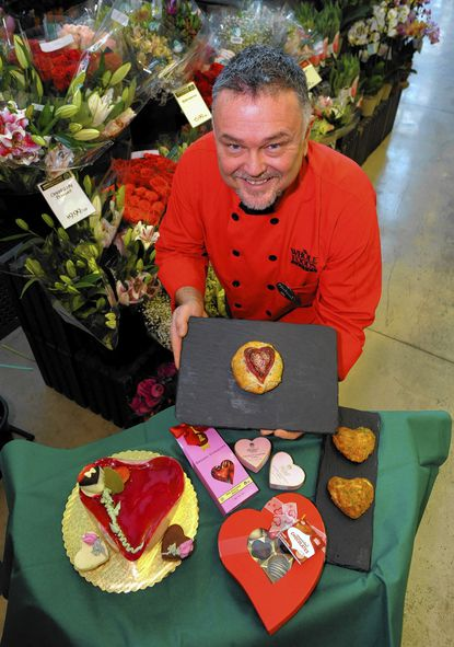 Michael Fowler, specialty team leader at Whole Foods in Harbor East, displays a Brie en Croute cherry and dark chocolate pastry that he created, along with a few of the many other Valentine's Day food items available at the store, including heart-shaped crab cakes (far right).