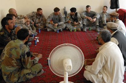 An Afghan national army soldier sits beside Lt. Abdul Qahar, ANA, Capt. Adam MacAllister, commander, Company C, 3rd Squadron, 61st Cavalry Regiment, Capt. Savins Girts, Observation Mentor Liasion Team, Capt. Visnakous Juris, OMLT, Lt. Brandon Loomis, 3-61, Interpreter Sultan Mahmoodtanha, and two Asymmetric Warfare Group workers as they speak with the two Nishagam Village elders and the head of the district center in Konar province, Afghanistan in 2009. (Evan Marcy/handout/Baltimore Sun).