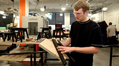 At Open Works, Harrison Tyler, the digital operations manager, holds a stool leg from a Room & Board job. The stool will be manufactured in the new commercial contract shop when it opens in early July.