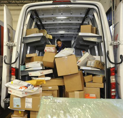 Linthicum, MD -- December 15, 2014 -- Julita Santiago, a courier for FedEx, is dwarfed by packages as she sorts them in her truck. She will be delivering to the Jessup area. The holiday season is in full swing at the Fed Ex facility, where workers are sorting packages and loading trucks for delivery. The company says that today is its busiest day of the year.