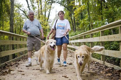 Bernie and Judi Fishman walk their dogs, Chloe and Buddy, along the new boardwalk at Robert E. Lee Park. The park reopens Friday.