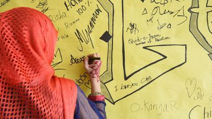 Freshman Nimra Hareem writes on a wall containing messages from other students during the third annual LanScape community arts and culture event May 1 at Lansdowne High School.