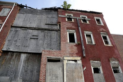 Boards cover the front end of a abandoned row homes near Baltimore's Hollins House, a high rise building housing seniors and persons with disabilities, which was toured by U.S. Housing and Urban Development Secretary Ben Carson in July.