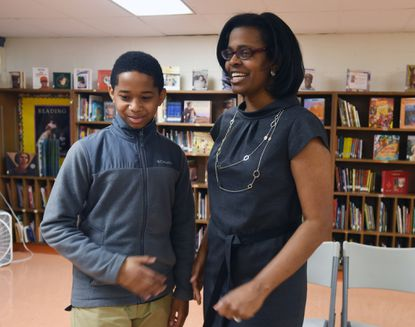 Baltimore City Public School CEO Sonja Santelises, right, talks with Hampstead Hill Academy student Adam Gousse, who received a free pair of glasses under a program that began last May.