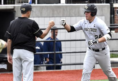 Wake Forest first baseman Gavin Sheets (24) is congratulated by the third base coach as he heads for home to score during the Atlantic Coast Conference baseball tournament against Georgia Tech in Louisville, Ky., on May 25, 2017.